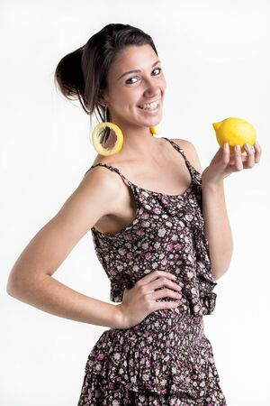 ear rings: A young model in the studio with lemon ear rings and a lemon in the hand