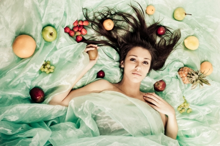 A young lady on green organza with fruit  Stock Photo - 17231937