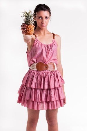 A young teenage model with a pineapple in her right hand Stock Photo - 17263028