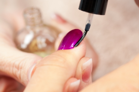 The beautician busy with the final touches of the manicure, putting on the cutex  Stock Photo