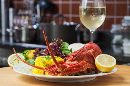 A nice, big plate filled with lobster, rice and a glass of white wine  Stock Photo