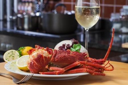 Een mooi, groot bord gevuld met kreeft, rijst en een glas witte wijn Stockfoto