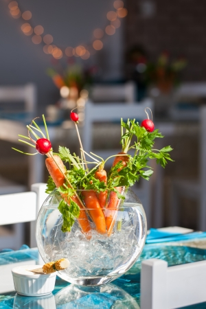 obtained: Carrot and berries ikebana decorations in a glass vase.