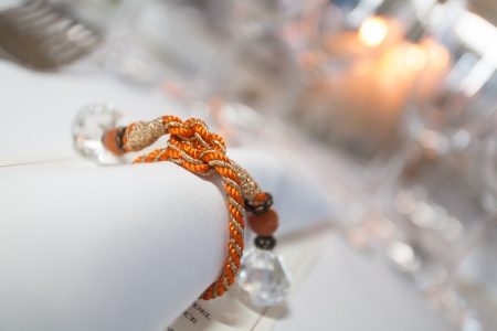 Serviette: Servilleta con velas y cuerdas de color naranja con diamantes. Foto de archivo