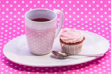 A cup of Cranberry  tea with a pink cupcake for ekstra sugar. photo