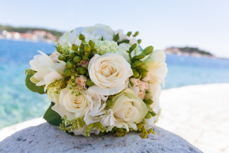 Wedding bouquet with different roses on a rock by the ocean. Stock Photo