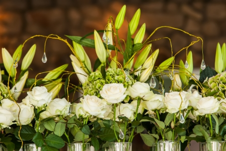 A whole bunch of roses in huge vases on a table with lillies. photo