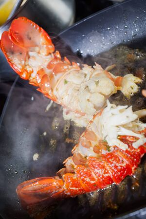 Crayfish being prepared in a a frying pan with oil. photo