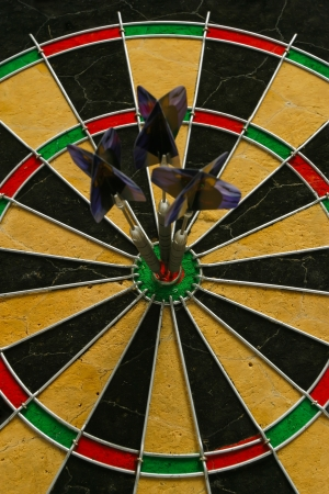 Three darts in the bull's eye of the dart board. photo