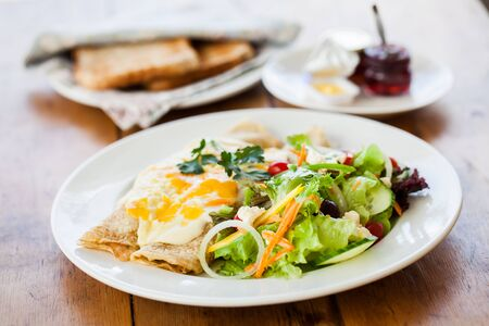 chees: Pancakes with filling and eggs served with a salad.