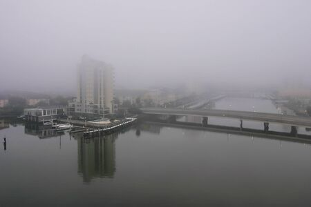 Foggy weather hanging over the buildings and harbor of the city. photo