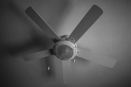 Black and white photograph of a fan hanging in a roof. photo