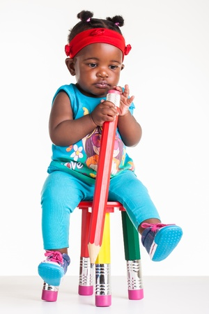 A little African baby with a huge pencil in the hands. photo