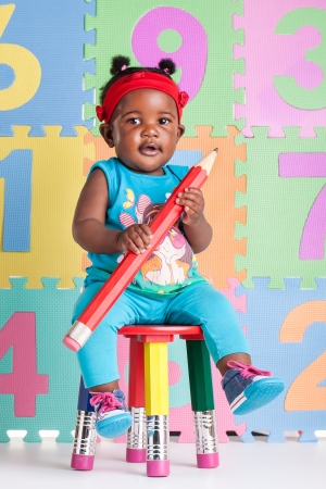 high chair: A little African baby with a huge pencil in the hands. Stock Photo