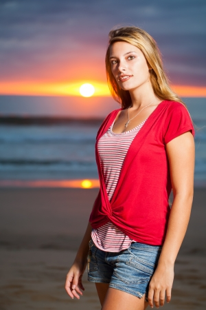A young girl on the beach with sunrise. photo
