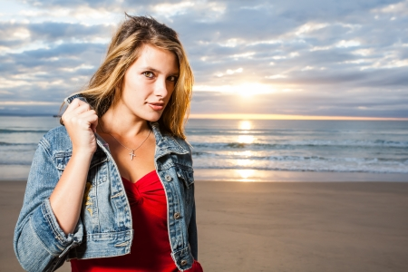 A sparkling, young girl on the beach with sunrise. photo