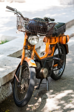 A orange scooter on a pavement of the streets in Bol. photo