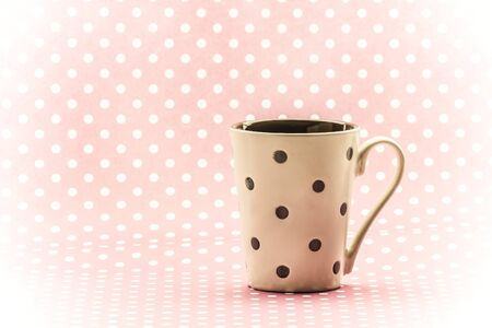 silently: A cream polkadot cup with a pink polkadot background