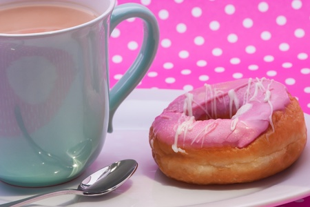 A cup of  tea with a pink doughnut for ekstra sugar. photo