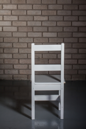 A slim white chair is standing towards the wall. photo