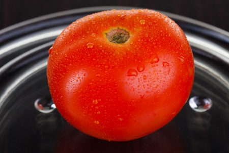 glas: One ripe red tomato on a glas plate. Stock Photo