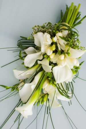 A big flower bouquet filled with cala lillies and other plants. photo