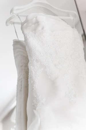 A close- up photograph of a wedding dress. photo