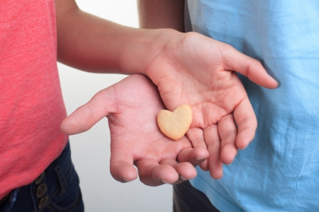 A small heart shortbread cookie being shared by a couple. photo