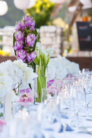A very nicely decorated wedding table with plates and serviettes. photo