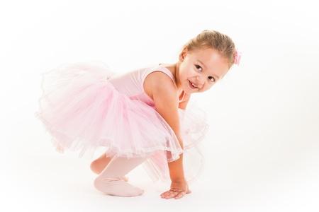 Een kleine roze ballerina in een speelse bui in de studio.