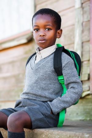 背面に彼の学校のバッグの階段に座ってください。