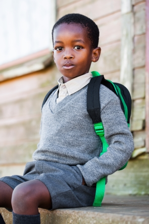 Sitting on the steps with his school bag on the back