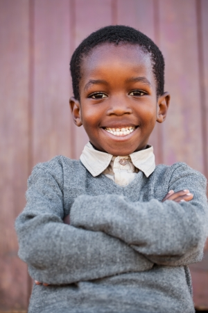 adolescent african american: A friendly school boy with crossed arms before the classroom