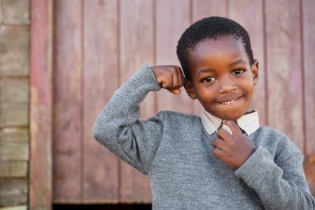 garcon africain: Forte petit homme montre ses muscles Banque d'images