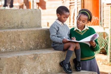 Niños ayudando: Una hermana est?n ayudando a su hermano peque?o con su trabajo a domicilio Foto de archivo