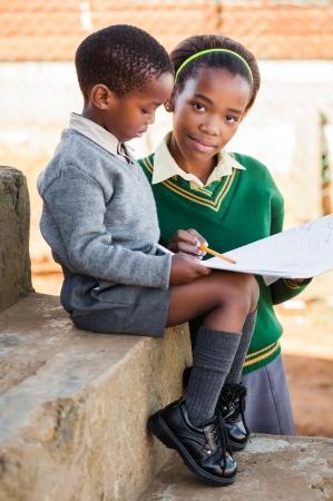 Niños ayudando: Una hermana están ayudando a su hermano pequeño con su trabajo a domicilio Foto de archivo