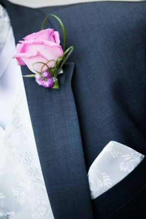 The groom in his tux with a pink rose through a pin. photo