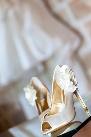 The beautiful shoes of the bride with flowers on the side. Stock Photo