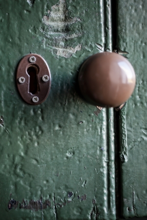 A very old door with the key hole and the knob in the centre. photo