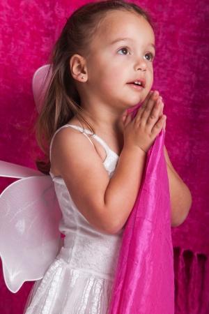 niño orando: Una chica en un traje de hadas blanco con fondo de color rosa.