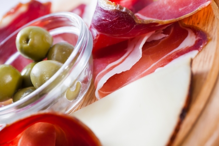 A big piece of curled bacon served with cheese and olives. photo
