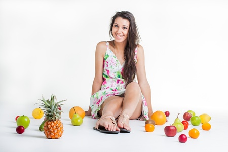 A young model in the studio on the floor with different fruits. photo