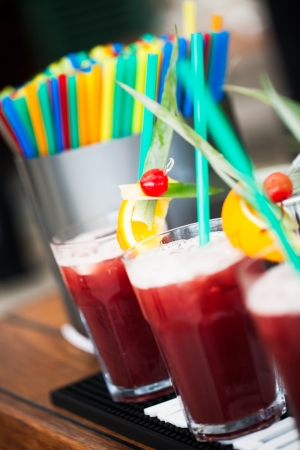 Big glasses filled with red cranberry juice and different colour straws. photo