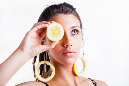 A young model in the studio with lemon ear rings and a lemon in the hand. photo