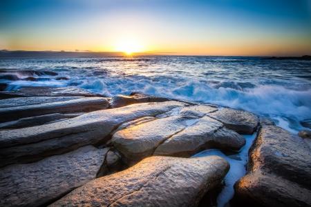 breaking dawn: el alba rompe sobre una costa rocosa y el mar vivo Foto de archivo