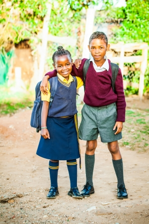 indigence: an african older brother proudly standing with his younger sister in their school uniform just before school starts