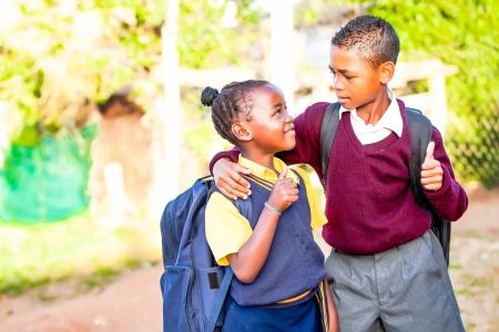 그의 여동생이 숭배과 자부심에 그에게 보이는 동안 최대 엄지 손가락으로 positivety을 보여주는 그의 여동생 주위에 자신의 팔을 젊은 아프리카 형제 스톡 콘텐츠
