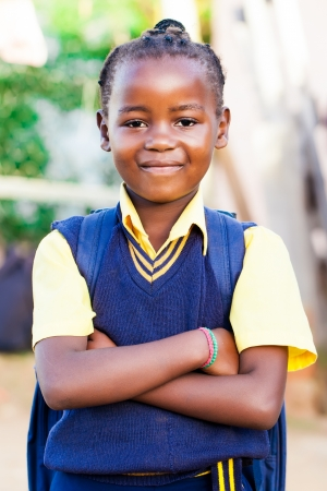 rural town: an young african girl in her blue and yellow school uniform and backpack, standing proud with her arms crossed