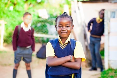彼女を見守る兄弟と彼女の黄色と青学校制服で誇らしげに立ってかなり若いアフリカの女の子 写真素材