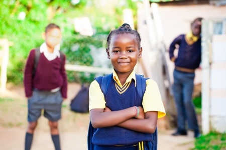 pretty young african girl standing proud in her yellow and blue school uniform with siblings watching over her  Reklamní fotografie